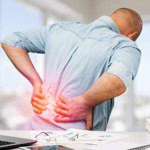 Business man with back pain an office . Pain relief concept